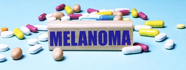 Um bloco de madeira com a palavra melanoma fica em uma superfície azul entre pílulas multicoloridas. conceito médico