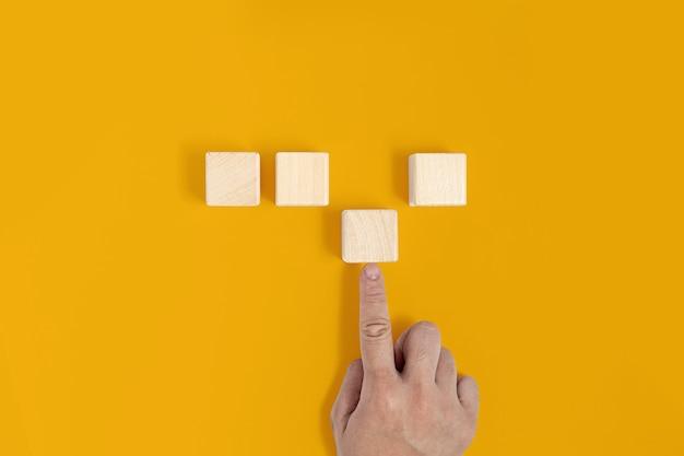 Um bloco de madeira quadrado é colocado sobre um fundo amarelo, a mão está empurrando o terceiro bloco de madeira no lugar. conceito de bloco de madeira, banner com espaço de cópia para texto, cartaz, modelo de maquete.