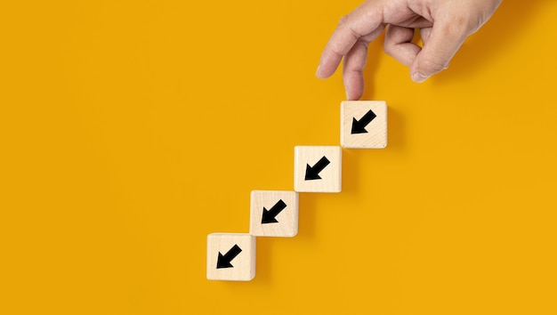 Um bloco de madeira quadrado é colocado sobre um fundo amarelo, no bloco de madeira mostrando uma seta para baixo e uma mão fazendo um movimento para baixo. banner com espaço de cópia para texto, cartaz, modelo de maquete.