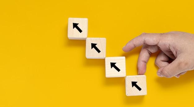 Um bloco de madeira quadrado é colocado sobre um fundo amarelo, no bloco de madeira mostrando uma seta para cima e uma mão fazendo um movimento para cima. banner com espaço de cópia para texto, cartaz, modelo de maquete.