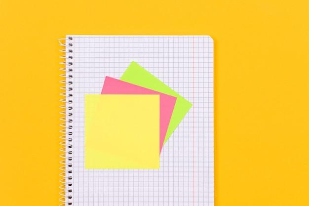 Um bloco de notas com notas adesivas na mesa amarela