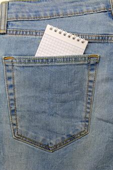 Um bloco de notas é inserido no bolso do jeans azul.