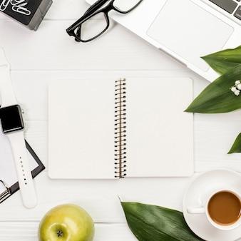 Um bloco de notas em espiral aberto rodeado de artigos de papelaria, maçã e relógio inteligente na mesa de escritório
