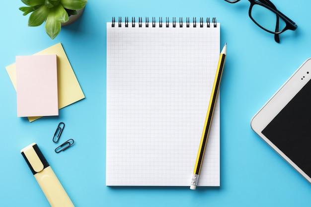 Um bloco de notas vazio aberto, caneta e tablet sobre uma mesa azul. fazendo uma lista ou planejamento.