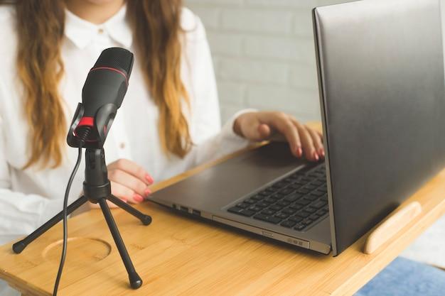 Um blogueiro grava um podcast em um microfone no interior de uma casa.