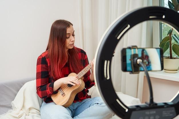 Um blogueiro músico grava uma transmissão online em um telefone celular em um suporte com uma lâmpada de anel, uma mulher toca ukulele para seus seguidores