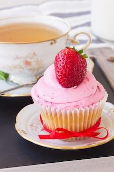 Um bolinho com morango fresco no prato e uma xícara de chá na mesa de madeira