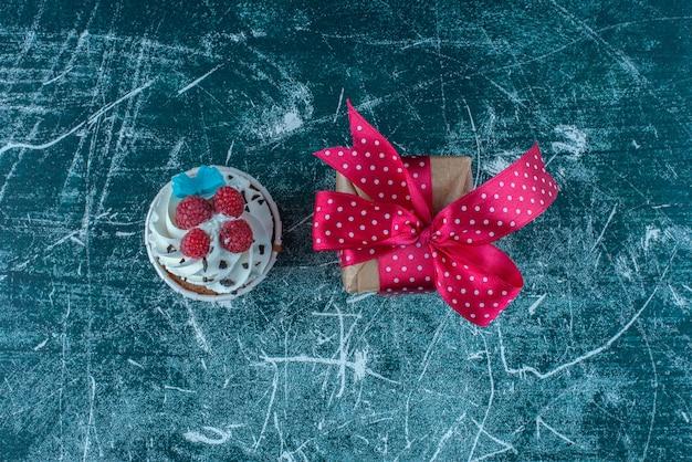 Um bolinho e uma pequena caixa de presente sobre fundo azul. foto de alta qualidade