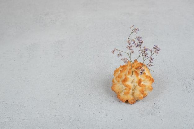 Um bolinho inteiro doce com flor murcha.