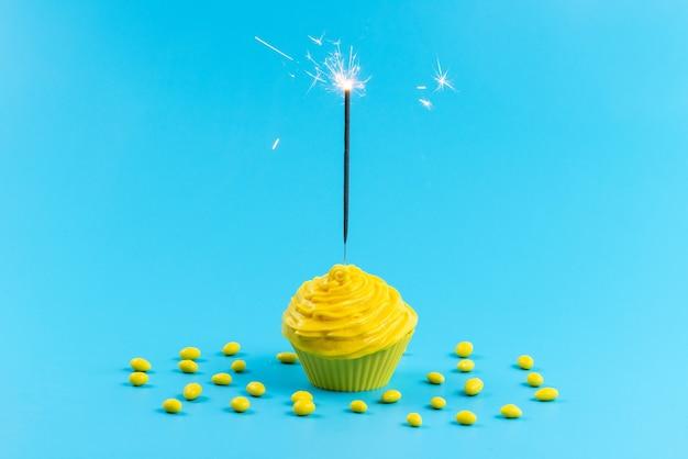 Um bolo amarelo de frente com doces amarelos na mesa azul, cor de biscoito doce de açúcar