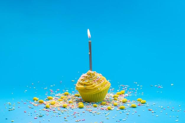 Um bolo amarelo de frente com vela sobre o bolo azul da mesa