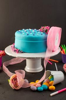 Um bolo de aniversário de frente para o azul com doces e velas na mesa escura.