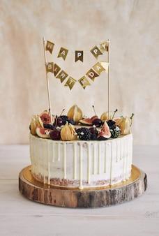 Um bolo de aniversário de frutas com cobertura de aniversário, frutas em cima e gotejamento branco sobre fundo bege