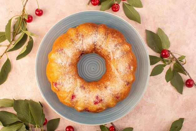 Um bolo de cereja com vista superior redondo formado dentro de um prato cinza na mesa rosa biscoito açúcar doce