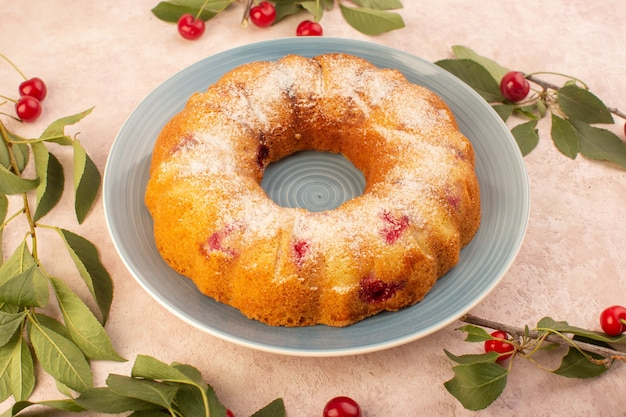 Um bolo de cereja com vista superior redondo formado dentro do prato na mesa rosa biscoito açúcar doce