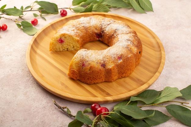 Um bolo de cereja frontal na mesa de madeira com cerejas frescas na mesa rosa