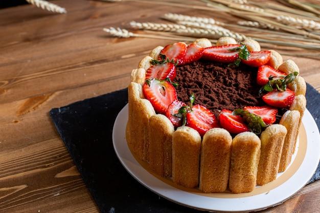 Um bolo de choco de vista frontal decorado com biscoitos de morangos vermelhos fatiados, gostoso dentro de um prato branco sobre a confeitaria de biscoito doce de mesa marrom