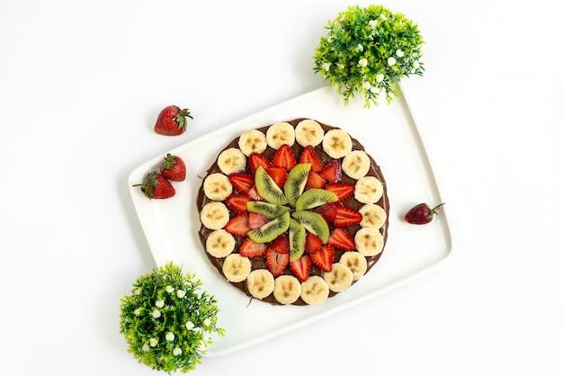 Um bolo de chocolate com frutas frescas elaborado com bananas frescas, morangos e kiwis em um prato branco com açúcar e sobremesa doce