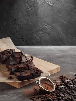 Um bolo de chocolate fatiado está sobre uma mesa cinza com gotas de chocolate e cacau.
