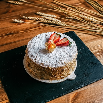 Um bolo de creme de vista frontal decorado com morangos fatiados delicioso bolo de aniversário dentro de aniversário de doçura de confeitaria de chapa branca no fundo marrom