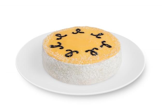 Um bolo de esponja redondo com creme encontra-se na chapa branca em branco