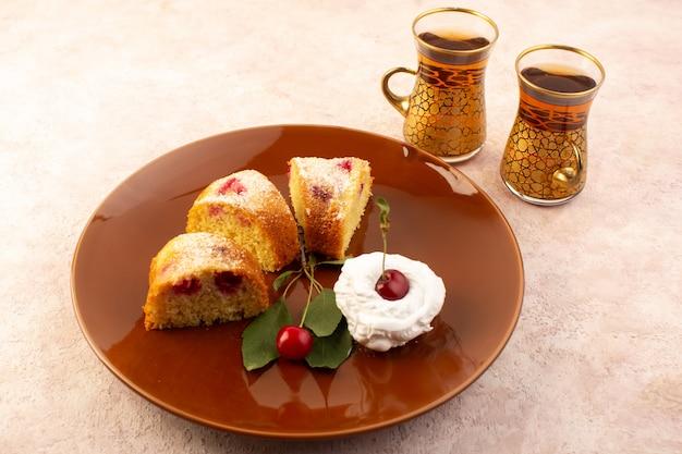 Um bolo de frutas assado delicioso fatiado com cerejas vermelhas e açúcar em pó dentro de um prato marrom redondo rosa