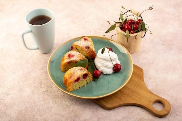Um bolo de frutas assado delicioso fatiado com cerejas vermelhas e açúcar em pó dentro de um prato redondo verde com chá rosa