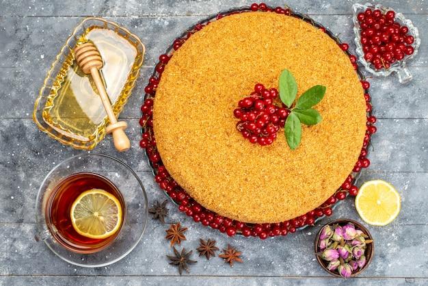 Um bolo de mel delicioso com vista de cima e assado com cranberries vermelhas na mesa cinza.