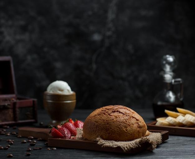 Um bolo de pão caseiro com morangos e bola de sorvete.