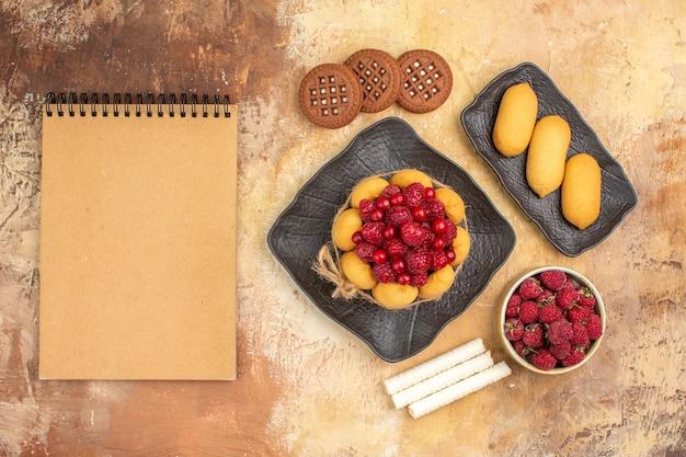 Um bolo de presente e biscoitos em pratos de frutas marrons e caderno na mesa de cores misturadas