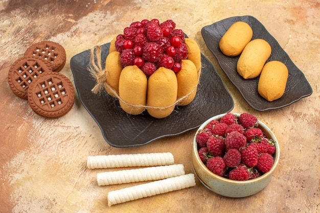 Um bolo de presente e biscoitos em pratos de frutas marrons em vista lateral da mesa de cores misturadas