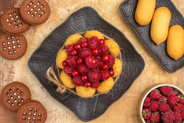 Um bolo de presente e biscoitos em pratos marrons frutas na mesa de cores diferentes