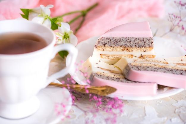 Um bolo doce rosa copo rosa com bule de chá e copo em cima da mesa