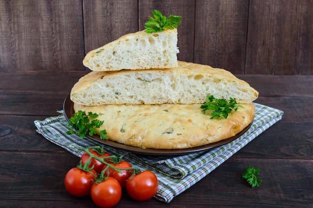 Um bolo liso grosso - pão árabe com verdes sobre um fundo escuro de madeira. um prato tradicional asiático.