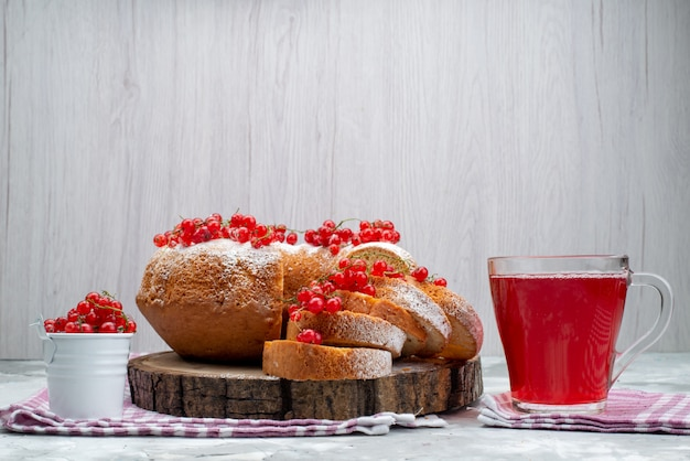 Um bolo redondo delicioso com cranberries vermelhas frescas e suco de cranberry na mesa de trabalho branco biscoito chá baga
