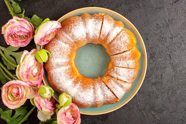 Um bolo redondo doce de vista superior com açúcar em pó no topo fatiado doce delicioso isolado dentro da placa junto com flores e biscoito de açúcar de biscoito de fundo cinza