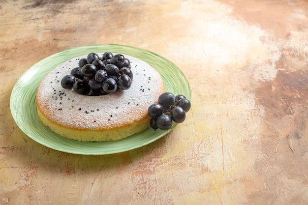 Um bolo um bolo apetitoso com uvas pretas açúcar de confeiteiro no prato