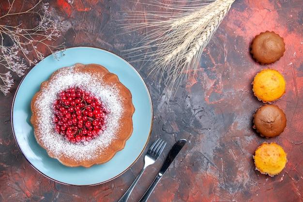 Um bolo um bolo com faca de groselha garfo quatro cupcakes