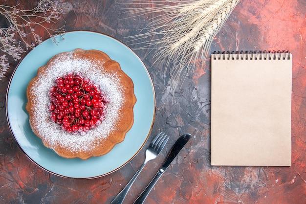 Um bolo um bolo com groselha caderno espigas de trigo ramos faca e garfo