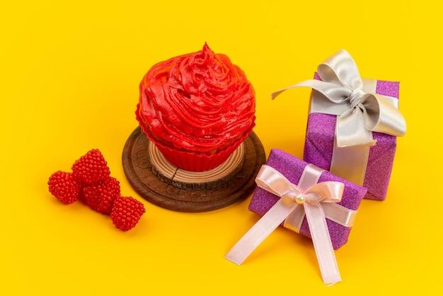Um bolo vermelho com framboesas frescas e caixas roxas de presente na mesa amarela