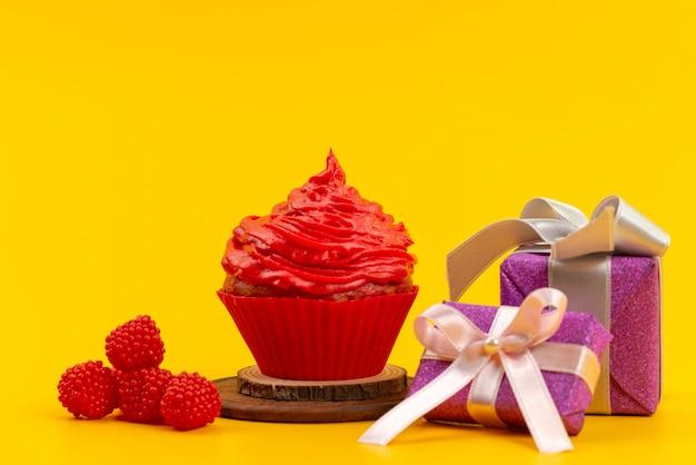 Um bolo vermelho de vista frontal com framboesas vermelhas frescas e caixas de presente roxas na mesa amarela