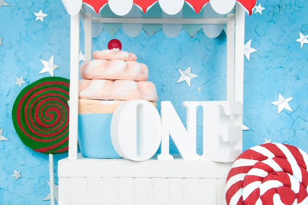 Um bom carrinho com as letras um com bolos e doces.