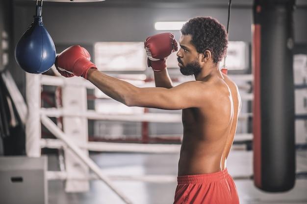 Um bom chute. kickboxer afro-americano se exercitando em uma academia e chutando o saco de areia