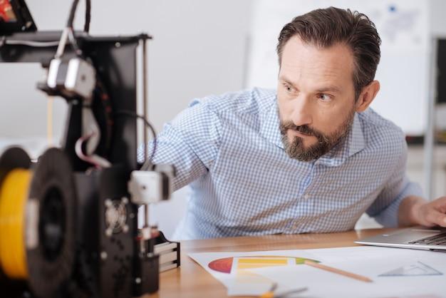 Um bom designer masculino sério olhando para a impressora 3d e verificando como ela funciona enquanto faz seu trabalho