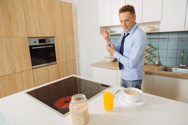 Um bom deus positivo olhando o homem parado perto do fogão e preparando o café da manhã enquanto cozinha