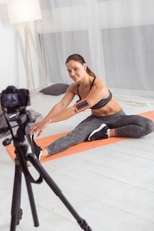 Um bom dia. mulher jovem e simpática, atlética, de cabelos escuros, sorrindo e se espreguiçando enquanto está sentada no tapete e fazendo um vídeo para seu blog
