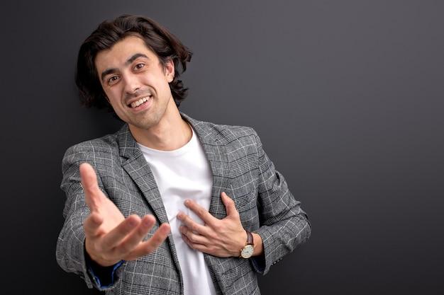 Um bom empresário empresário dá as boas-vindas aos novos funcionários estendendo os braços, chefe confiante em terno formal isolado no fundo preto