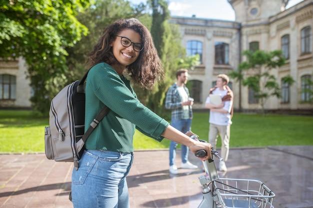 Um bom passeio. uma jovem mulata sorridente andando de bicicleta e se sentindo alegre