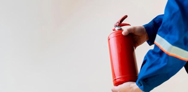 Um bombeiro segurando um extintor de incêndio, trabalho seguro e conceito de precauções