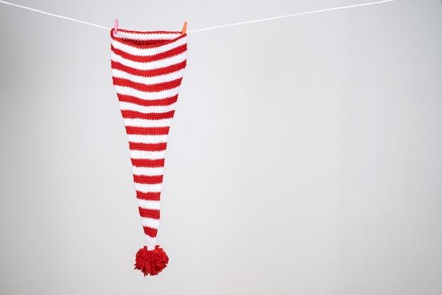 Um boné listrado vermelho e branco com uma cauda longa e um grande pompom vermelho pendurado em uma corda branca